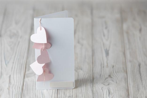 木製のピンクのハートで飾られたバレンタインデーのグリーティングカード