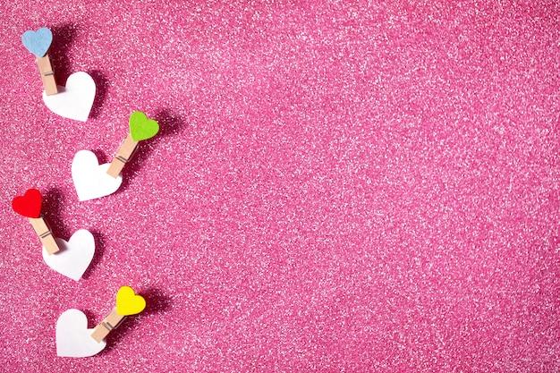 발렌타인 데이 인사말 카드입니다. 핑크 반짝이 배경에 clothespins에 4 개의 하트. 공간을 복사하십시오.