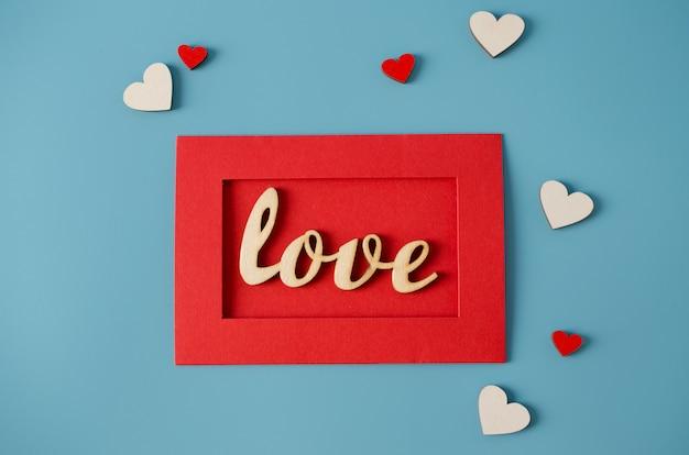 Открытка на день святого валентина. красный конверт с любовью сообщение и деревянные слухи на синем фоне.