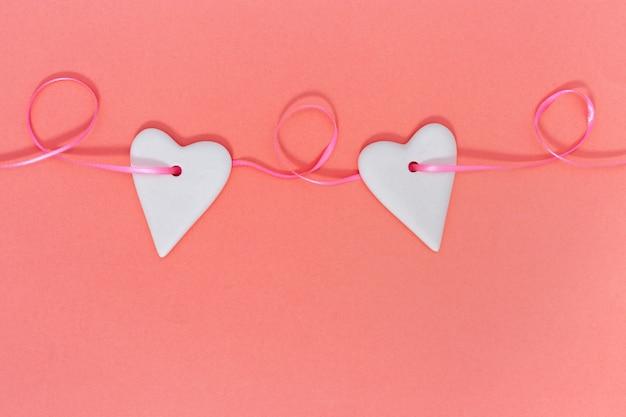 バレンタインデーのグリーティングカード、ハートの誕生日はピンクのリボンに掛かっています。サンゴの生きている色付きの背景にコピースペース。