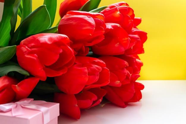 Формат поздравительной открытки. букет из красных тюльпанов крупным планом и подарочной коробке, желтый фон.