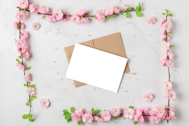 Greeting card in frame made of spring pink cherry blossom branches on white marble background. flat lay. top view. holiday or wedding layout with copy space