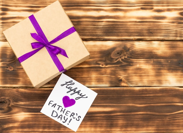 Greeting card for happy father's day with a gift box on a rustic wooden tabletop