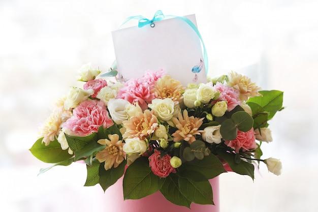 花のグリーティングカード。お祝いのメモ。カード付きのチューブに大きな美しい花束。誕生日の花。母の日のためのブーケ。休日のコンセプト。3月8日。おめでとうございます。