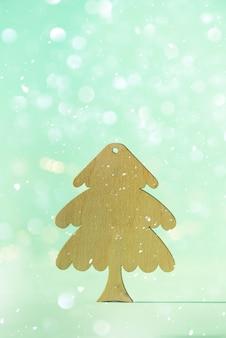 ミニマルスタイルのグリーティングカード。コピースペースで青い背景に木製のクリスマスツリー