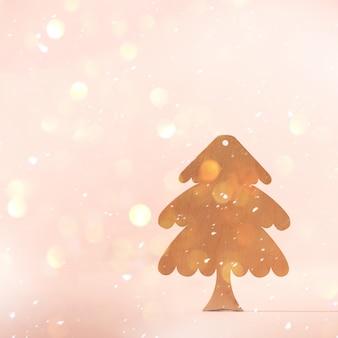 ミニマルスタイルのグリーティングカード。コピースペースとピンクの背景に木製のクリスマスツリー