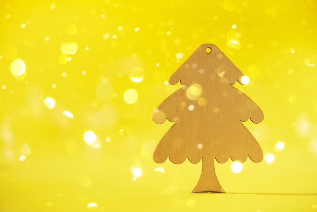 ミニマルスタイルのグリーティングカード。コピースペースと黄色の背景に木製のクリスマスツリー