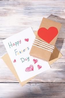 Открытка от ребенка и подарок в крафтовой бумаге с красным сердцем