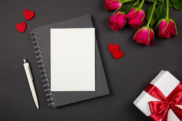 グリーティングカードのモックアップと赤いリボン、ハート、暗い表面にバラのギフトボックス