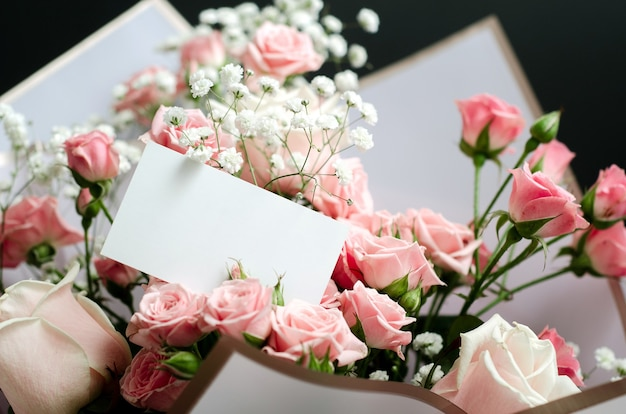 Greeting card mockup in a bouquet of pink roses, close-up photo