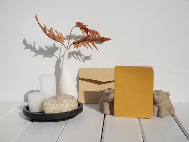 Макет поздравительной открытки, каменный подиум, свадебные канцелярские принадлежности, пригласительный конверт, ваза из высушенных листьев филодендрона, свечи на внутренней поверхности белого деревянного стола с длинной тенью