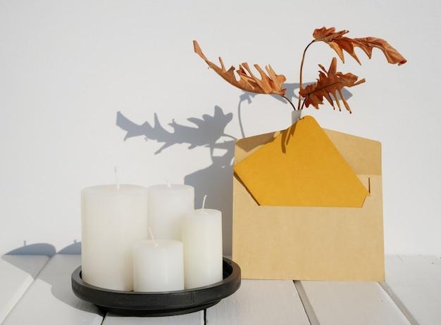Макет поздравительной открытки, свадебные канцелярские принадлежности, пригласительный конверт, ваза из сухих листьев филодендрона, свечи на внутренней поверхности белого деревянного стола с длинной тенью