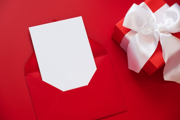 グリーティングカードのモックアップ、封筒に白い空白のカード、赤い背景のギフトボックス。フラットレイ、上面図。
