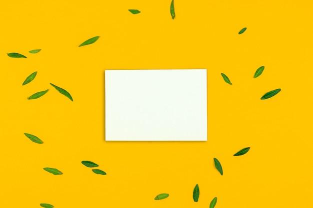 デスクトップ上の緑の葉、オレンジまたは黄色の背景、白紙、コピースペースの写真とグリーティングカードのモックアップ