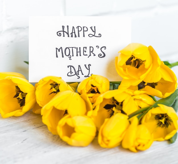 Greeting card for mother's day and yellow tulips on wooden table