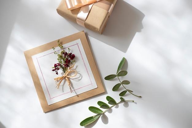 グリーティングカード、紙の封筒、花、白い背景にパステル。フラットレイ、上面図、コピースペース。ラブレター、ロマンスのコンセプト。
