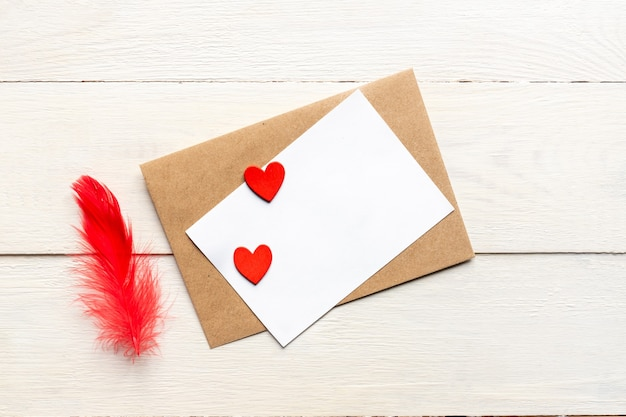 Greeting card template with craft paper envelope and bright red hearts and feather