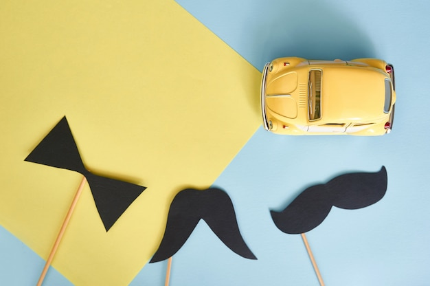 Greeting card top view with yellow toy car and black paper mustache