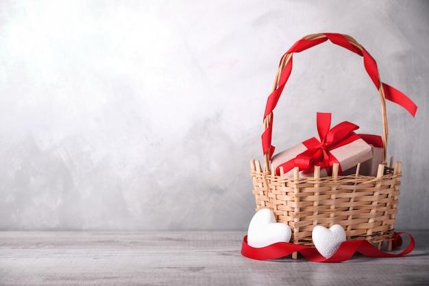 Открытка ко дню святого валентина с сердечками, бокалом и подарками в корзине. с пространством для ваших текстовых поздравлений
