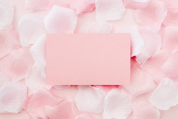 Greeting card on white and pink rose petals