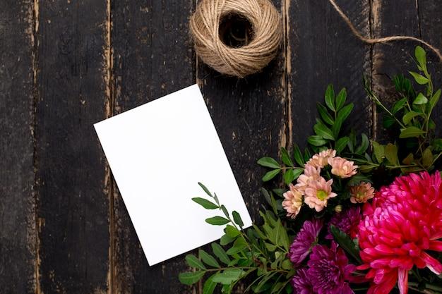 어두운 빈티지 나무에 꽃의 부케와 인사말 카드