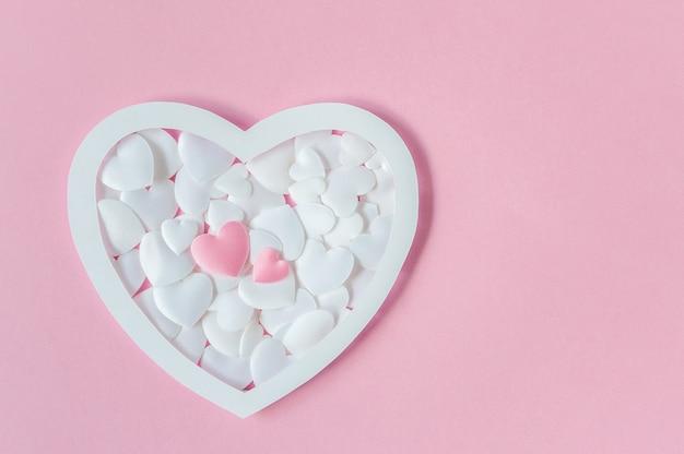 ピンクと白の心とピンクの背景上のテキストのためのスペースのグリーティングカード。上面図。平干し。バレンタインデーや母の日のコンセプト。