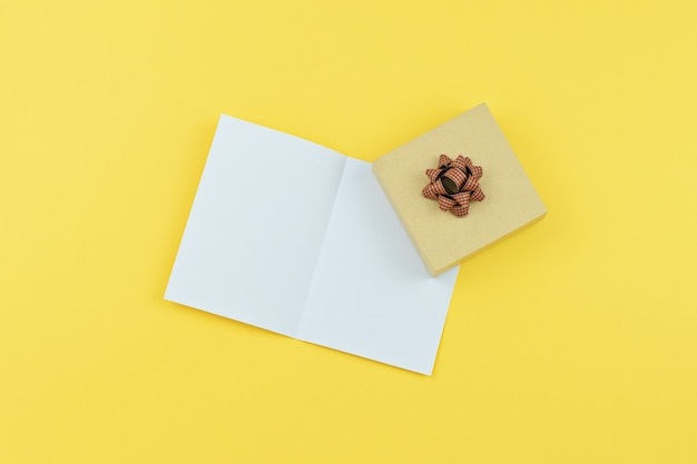 Greeting card with copy space and gift box on yellow