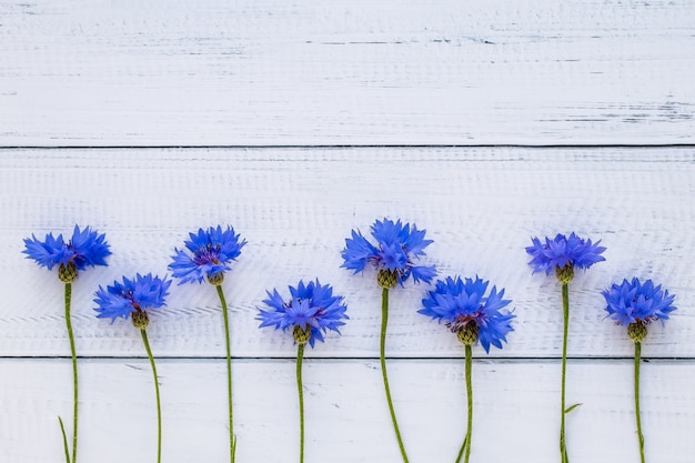 Greeting card with cornflowers on a wooden board, floral frame