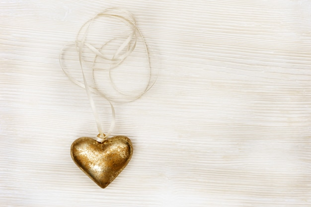 Greeting card with gold heart with ribbon and space on old wooden background. top view.