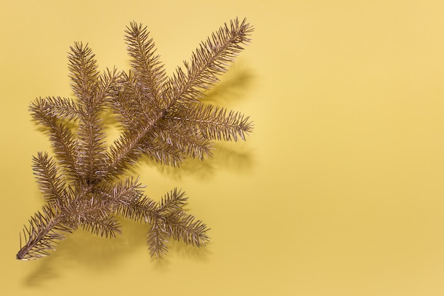 Greeting card with golden  christmas evergreen branch on yellow surface