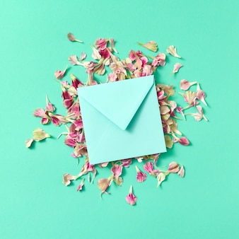 Поздравительная открытка с конвертом ручной работы на лепестках цветов на бирюзовом фоне и копией пространства. плоская планировка. макет.