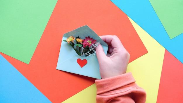 심장 모양 및 꽃 봉투를 들고 손으로 인사말 카드.