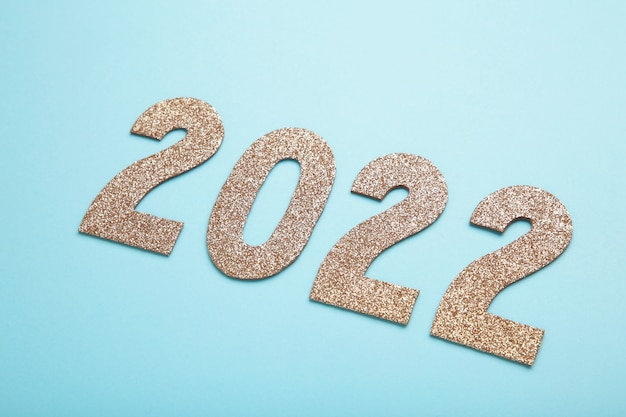 Greeting card with - happy new year with numbers 2022 in gold glitter. minimal holiday concept. top view