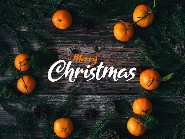 Greeting card with the inscription merry christmas on a wooden background with fir branches tangerines