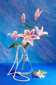 Открытка с цветами лилии и ожерельем на синем пространстве