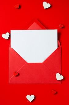 Открытка с любовью. красный конверт с пустой картой. вид сверху с пространством для ваших поздравлений.