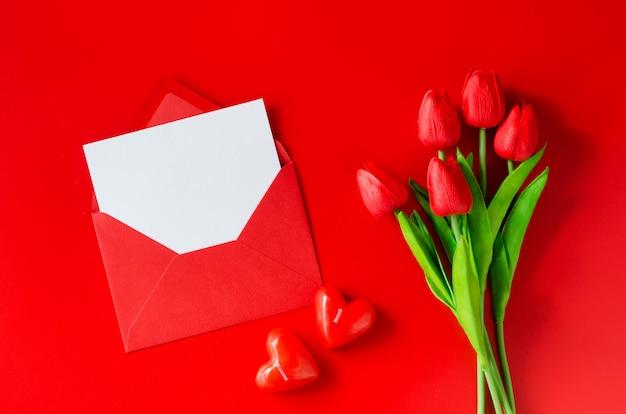 Открытка с любовью. красный конверт с чистого листа, букет тюльпанов и свечи в форме сердца.