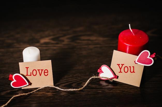 Открытка с красными сердцами для графического дизайна на коричневом деревянном столе.