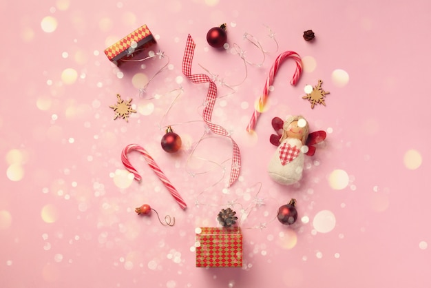 Greeting card with snow, lights bokeh for new year party. christmas gifts, decorative elements and ornaments on pink background.