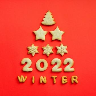 赤い背景の上のクッキーで作られたグリーティングクリスマスカード。 2022年のコンセプト。クッキーのクリスマスツリーの形。上面図、コピースペース