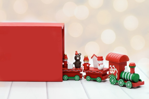 Greeting christmas card: santa claus red wooden toy train with carriages leaves red gift bag