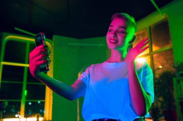 挨拶。ネオンライトのインテリアでスタイリッシュな女性の映画のような肖像画。シネマエフェクトのようなトーン、明るいネオネードカラー。室内のカラフルな照明でスマートフォンを使用した白人モデル。若者文化。