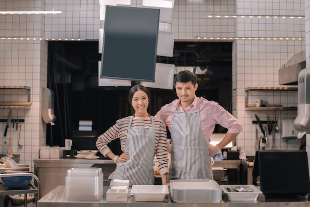 クライアントへの挨拶。彼らのカフェテリアのクライアントに挨拶する若いハンサムな成功した起業家のカップル
