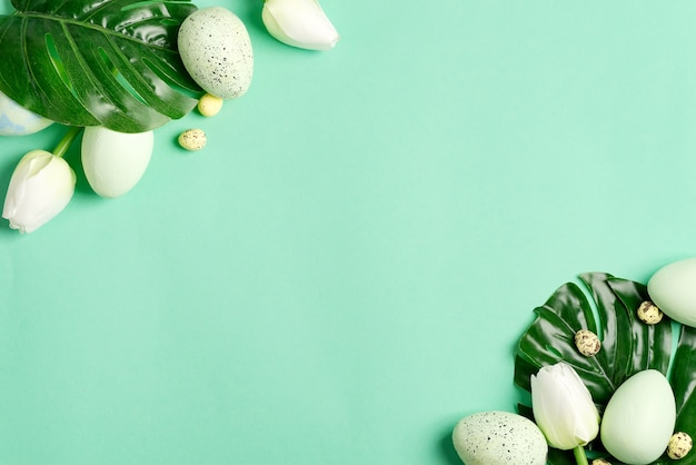 Greeting composition from small quail eggs, green eggs and green tropical leaf plant on a pastel turquoise background.