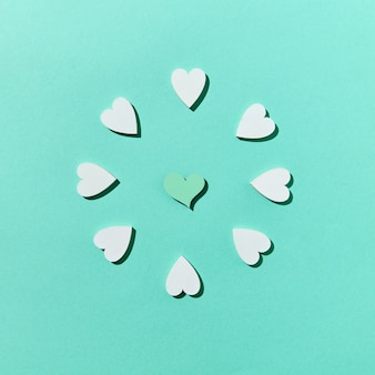 Поздравительная праздничная праздничная композиция из гипсовых сердечек ручной работы на пастельно-бирюзовой стене с жесткими тенями, копией пространства. вид сверху. валентина