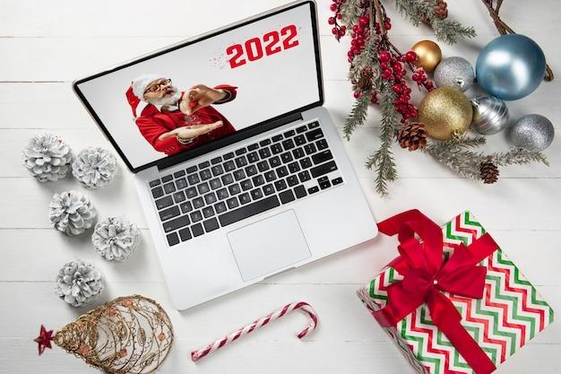 Приветственный флаер для рекламы. концепция рождества, новый год 2021, зимнее настроение, праздники. copyspace, открытка. санта на экране устройства с волшебным порошком. приветствие рождественских праздников. вид сверху