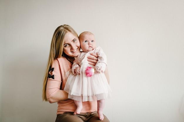Поздравление для мамы с новорожденной девочкой, которая держит цветок. день матери. счастливый семейный портрет, концепция семейного отдыха.
