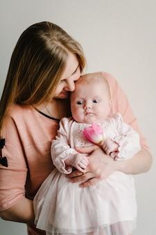 花を持った生まれたばかりの女の赤ちゃんを持つお母さんへのご挨拶。女性の日。母の日。幸せな家族の肖像画、家族の休日の概念。