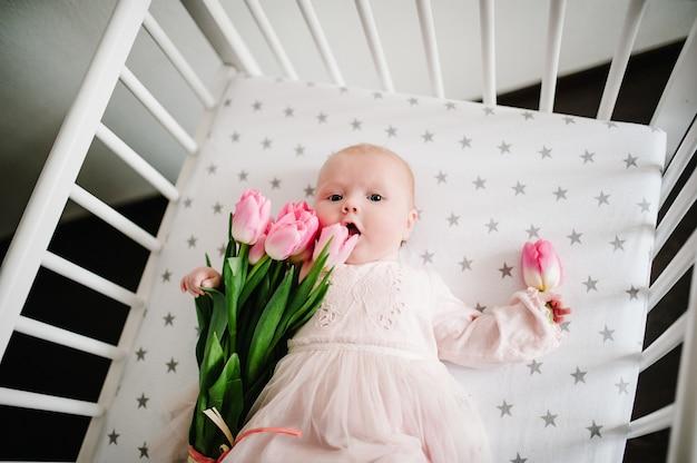 Поздравление матери с новорожденной девочкой, которая держит цветок и лежит на кровати с букетом розовых тюльпанов. женский день. день матери.