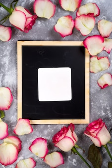 Greeting frame with fresh roses flowers and petals around on a gray marble background. flat lay.